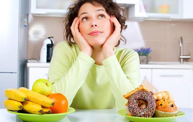 Beautiful Young Woman choosing between Fruits and Sweets