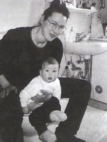 Взрослый сидит на унитазе, держа ребенка перед собой