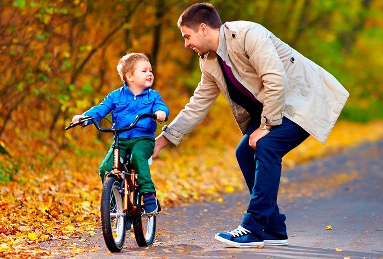 ребенок учится кататься на велосипеде