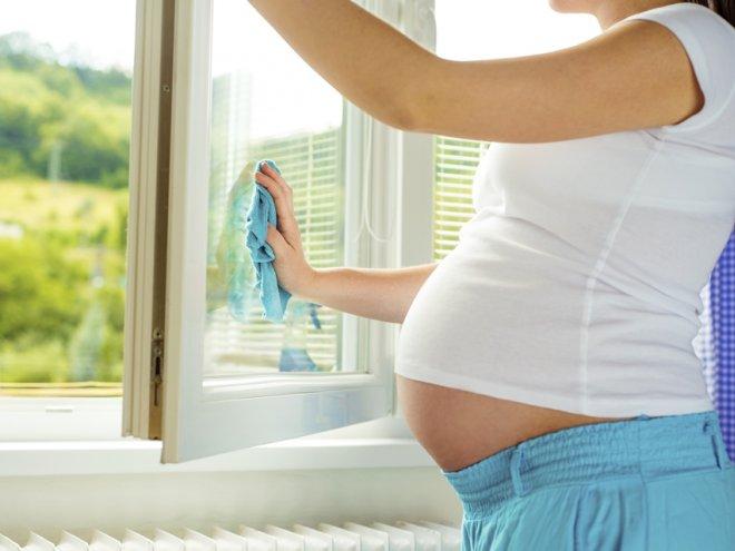 беременная женщина моет окна