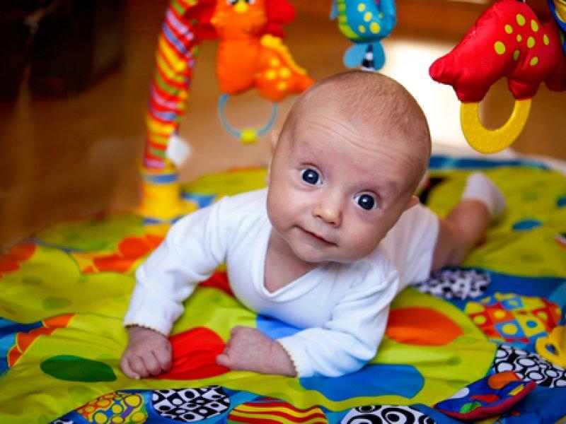 ребенок на животике рядом игрушки