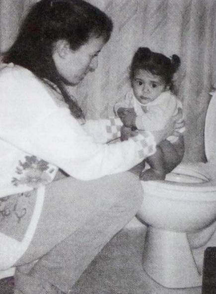 Малыш сидит на унитазе, а взрослый перед ним
