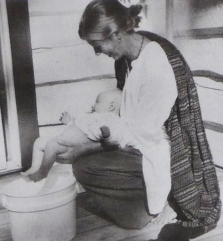 Малыш лежит на руках горизонтально